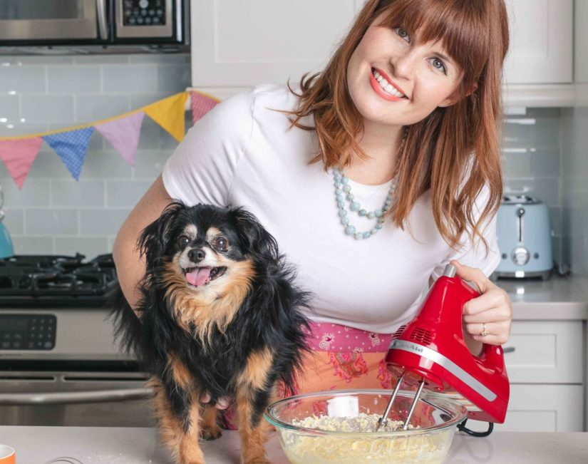 A woman and her dog are mixing some cake batter in the kitchen.