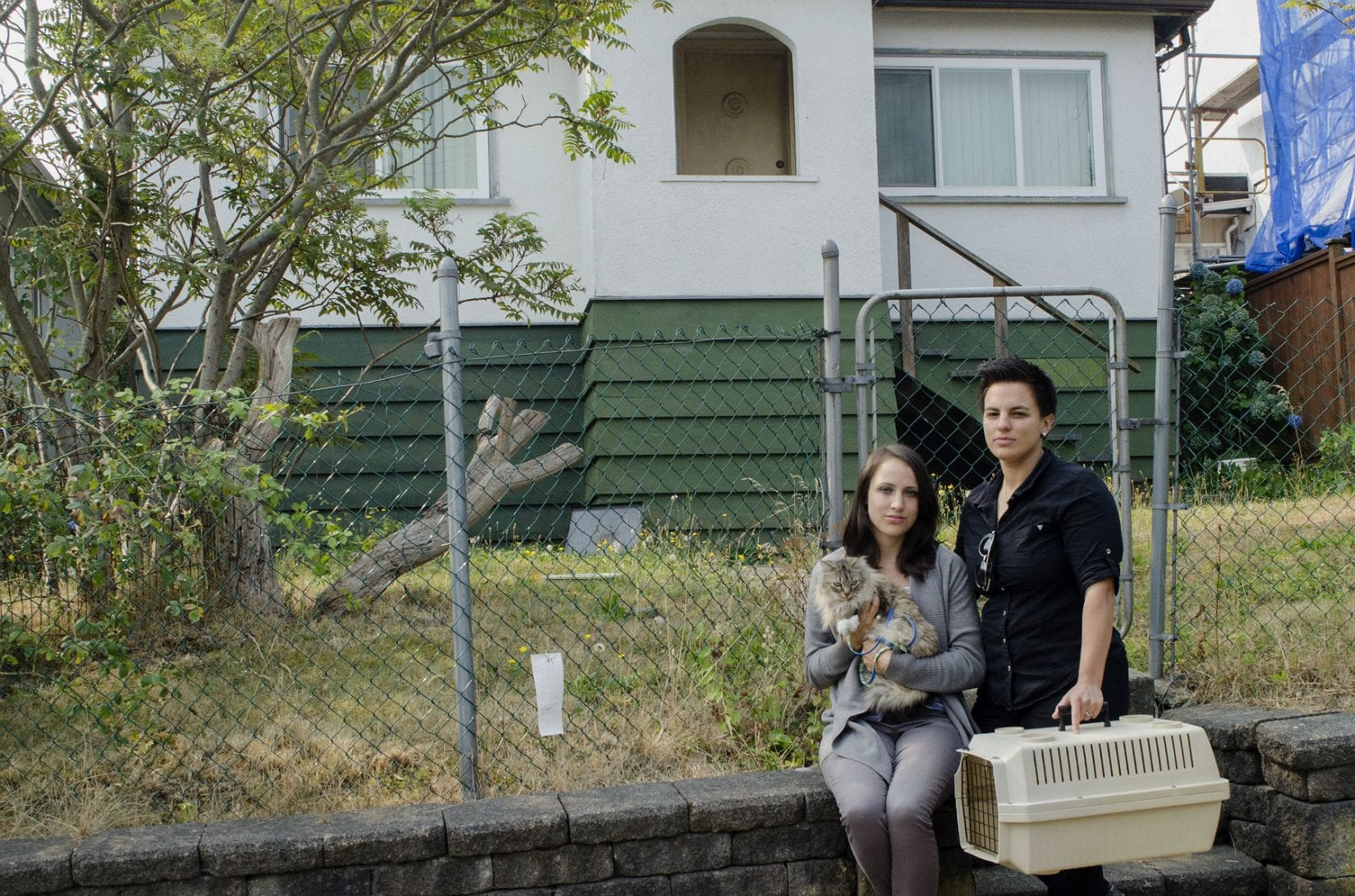 Cat and two women outside of a house