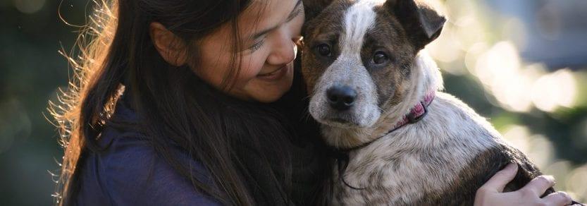 Girl hugging dog looking at the camera