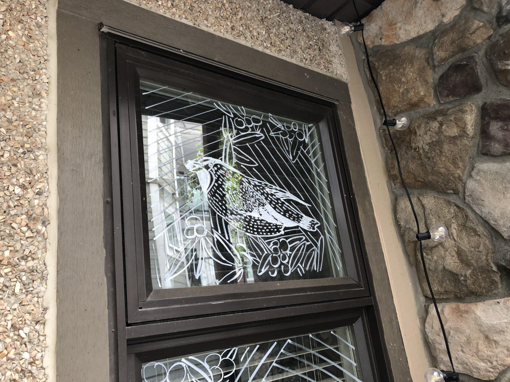 Hand-drawn design on a window to prevent bird strikes