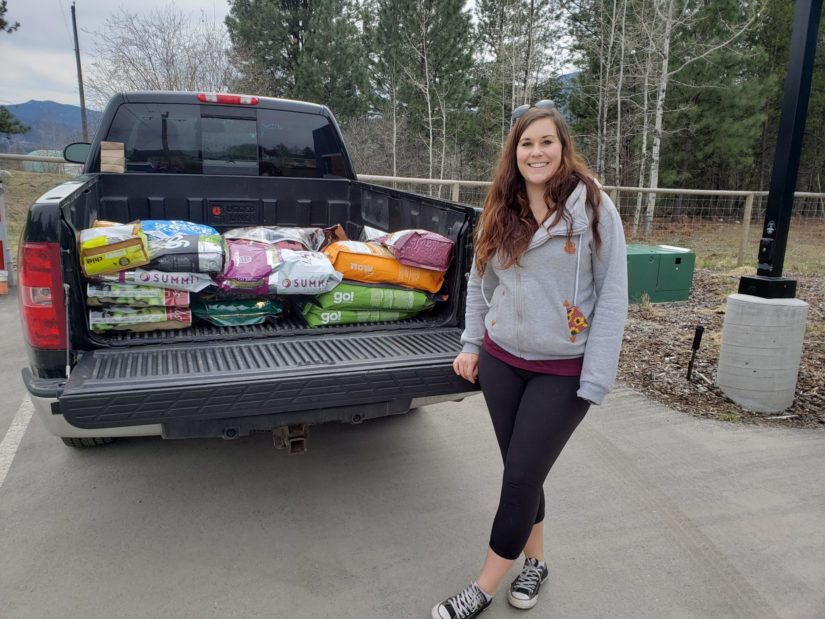 woman stands in front truck with donation of pet food